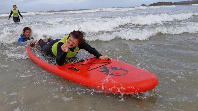 """Christiane, une résidente de l'Ehpad de Dol-de-Bretagne, en Ille-et-Vilaine, ern pleine session de """"surf thérapie"""" à Saint-Malo, le 25 septembre 2019. (SOLENNE LE HEN / FRANCEINFO)"""