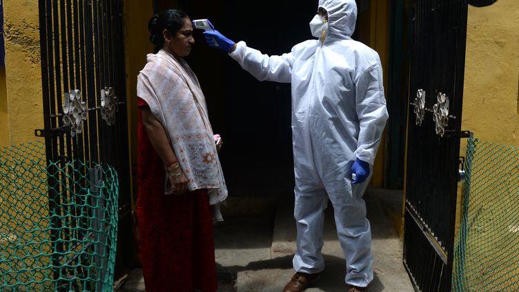 Un médecin vérifie la température d'une patiente dans le cadre d'un contrôle lié au Covid-19, le 29 juin 2020 à Chennai (Inde). (ARUN SANKAR / AFP)
