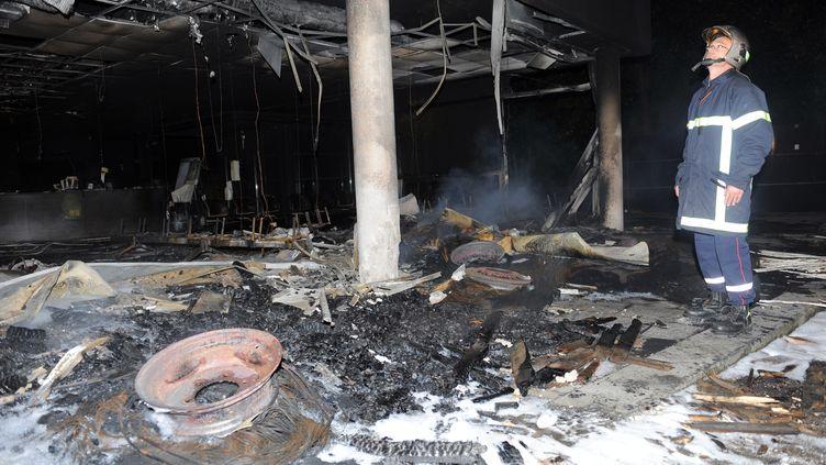 Un pompier inspecte les décombres du centre d'impôts de Morlaix (Finistère), incendié par des agriculteurs en colère, le 20 septembre 2014. (FRED TANNEAU / AFP)