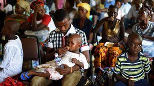 Un enfant ayant survécu à Ebola est nourri par un autre survivant, le 11 novembre 2014, dans un centre de traitement à Hastings (Sierra Leone). (FRANCISCO LEONG / AFP)