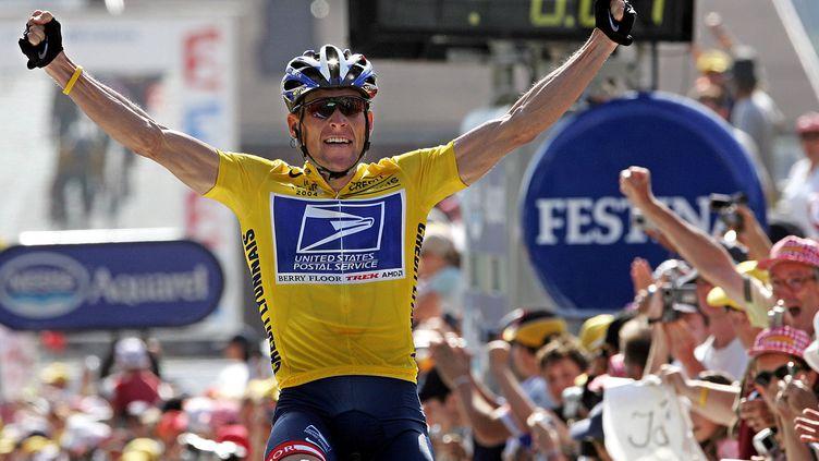 Lance Armstrong célèbre sa victoire au Tour de France, sur les Champs-Elysées, à Paris, le 22 juillet 2004. (PATRICK KOVARIK / AFP)