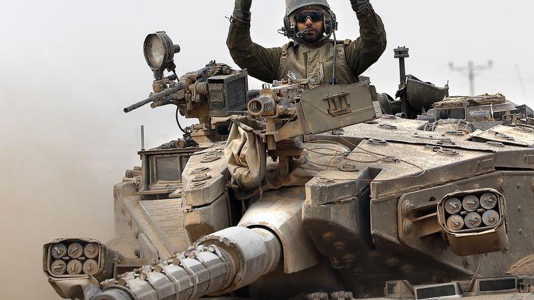 """Du haut de son char, un soldat israélien fait le """"V"""" de la victoire, le 5 août 2014, alors qu'il quitte la bande de Gaza. (THOMAS COEX / AFP)"""