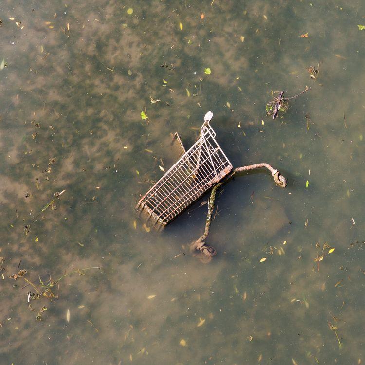 Un chariot de supermarché, dans une rivière sale. Les collapsologues envisagent l'effondrement, à court terme, de la civilisation industrielle. (FHM / MOMENT RF / GETTY IMAGES)