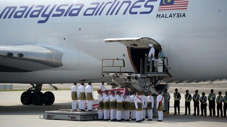 Des soldats portent les cercueils des victimes malaisiennes du crash du vol MH17,le 22 août 2014, à l'aéroport de Kuala Lumpur (Malaisie). (MANAN VATSYAYANA / AFP)