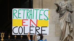 """Un homme brandit une pancarte """"Retraités en colère""""lors d'une manifestation contre la réforme des retraites, le 14 juin 2018 à Paris. (ZAKARIA ABDELKAFI / AFP)"""