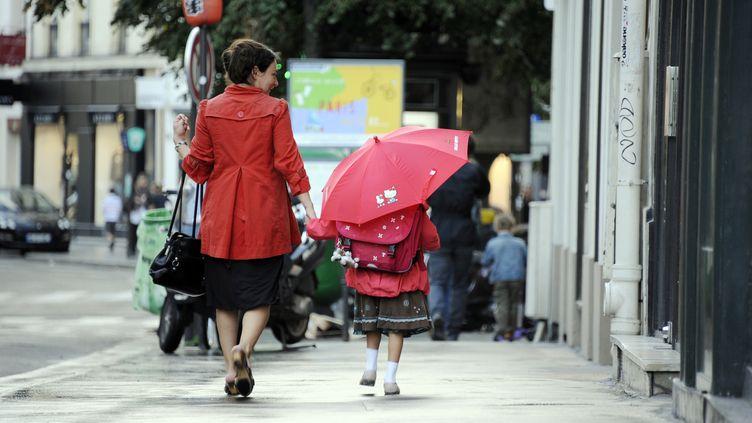 Une mère et sa fille se rendent à l'école, le 5 septembre 2011, à Paris. (Photo d'illustration) (JOHANNA LEGUERRE / AFP)