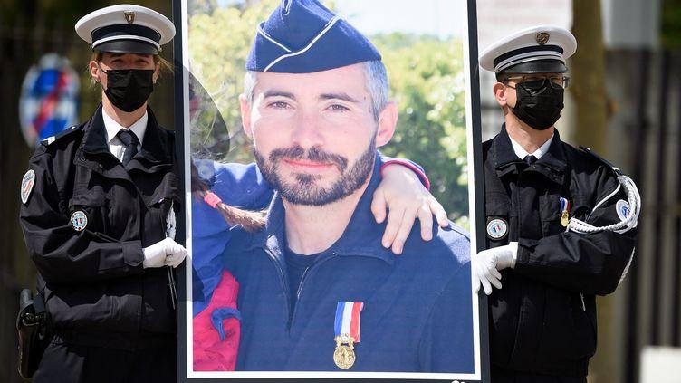 Des policiers portent le portrait d'Eric Masson, agent de police tué en intervention le 5 mai, lors d'une cérémonie d'hommage national, le 11 mai 2021 à Avignon. (NICOLAS TUCAT / POOL / AFP)