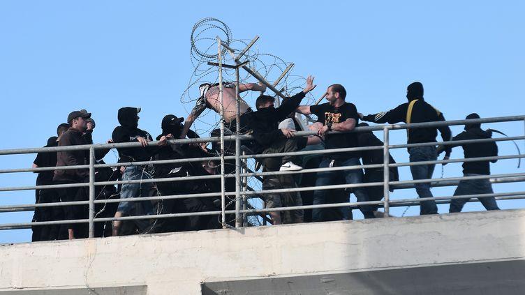Deux groupes de fans du PAOK et de l'AEK en décousent autour du stade avant la finale (SAKIS MITROLIDIS / AFP)