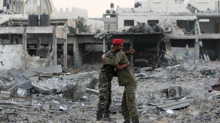 Deux policiers du Hamas de retour dans leur quartier général d'Al-Saraya, à Gaza,s'embrassent, jeudi 22 novembre. (MAHMUD HAMS / AFP)
