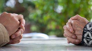 Les mains d'une dame âgée, dans un Ehpad d'Occitanie, et de son fils, le 23 octobre 2019. (PATRICIA HUCHOT-BOISSIER / HANS LUCAS / AFP)