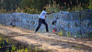 Un migrant tente de passer la clôture de barbelés à la frontière entre la Hongrie et la Serbie, à Roszke, le 27 août 2015. (ATTILA KISBENEDEK / AFP)