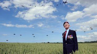 Frederick Glover, ancien combattant britannique de la Seconde Guerre mondiale, pose devant des parachutistes lors d'une commémoration du 70e anniversaire du débarquement allié en Normandie, le 5 juin 2014 à Ranville (Calvados). (THOMAS BREGARDIS / AFP)