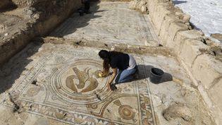 Une archéologue israélienne dévoile le sol en mosaïque d'une église byzantine dans la ville israélienne de Beit Shemesh, le 23 octobre 2019. (MENAHEM KAHANA / AFP)