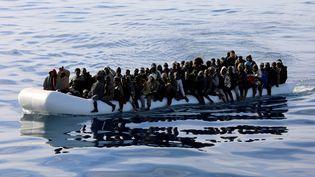 Des migrants sur un canot pneumatique au large des côtes libyennes, le 15 janvier 2018. (HANI AMARA / REUTERS)