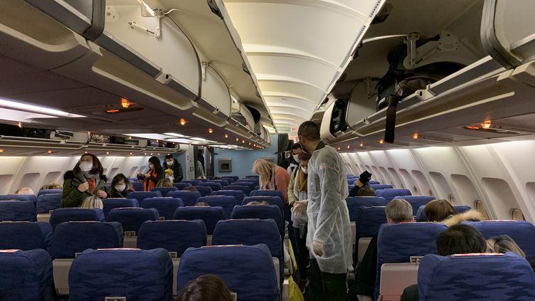 Des ressortissants français de la ville chinoise de Wuhan dans l'avion dépêché par la France pour les rapatrier en métropole, le 31 janvier 2020. (HECTOR RETAMAL / AFP)