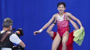 L'entraîneur deQuan Hongchan la porte en triomphe à l'issue de sa victoire en finale de l'épreuve de plongeon haut vol à 10 m, le 5 août 2021. (XU CHANG / XINHUA / AFP)