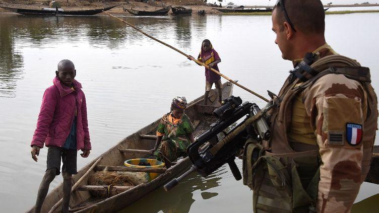 Un soldat français de l'opération Barkhane au port de Korioumé à Tombouctou, avec des habitants de la ville. Photo prise le 9 mars 2016. (PASCAL GUYOT / AFP)