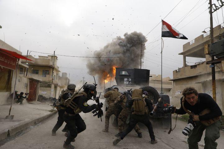 Irak, 2016. Mossoul. Explosion d'une voiture kamikaze à l'avant d'une colonne de la Golden Division. Au premier plan, le photographe Antoine Chauvel, fils de Patrick Chauvel. (PATRICK CHAUVEL)