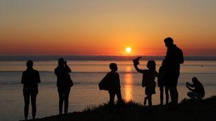 Une famille regarde le coucher de soleil depuis la dune du Pyla. (illustration) (LUDOVIC MARIN / AFP)