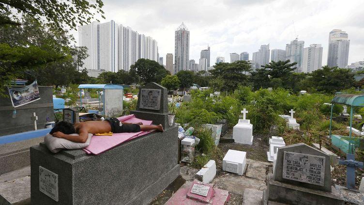 Un jeune homme est allongé sur une pierre tombale, rendant hommage à un proche disparu. La scène se passe quelques jours avant la Toussaint 2016, la plupart des Philippins ayant droit à plusieurs journées chômées avant et après le 1er novembre pour se rendre dans les cimetières, y nettoyer les tombes, les fleurir et même y passer la nuit. Le jour J, dès l'aube, les familles s'installent autour des sépultures, allument des bougies, fument, jouent aux cartes, dansent ou chantent pour honorer les âmes des défunts. (Bullit Marquez/AP/SIPA)