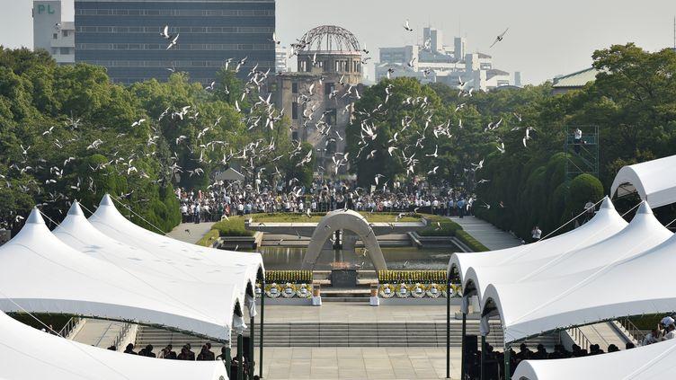 Des colombes s'envolent au-dessus du Mémorial de la paix, à Hiroshima, lors de la cérémonie marquant le 70e anniversaire du largage de la bombe atomique au-dessus de la ville. (KAZUHIRO NOGI / AFP)