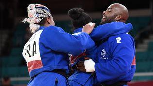 Romane Dicko, Sarah-Leonie Cysique et Teddy Riner fêtent la victoire sur le Japon et la médaille d'or dans l'épreuve mixte par équipes, le 31 juillet 2021. (FRANCK FIFE / AFP)