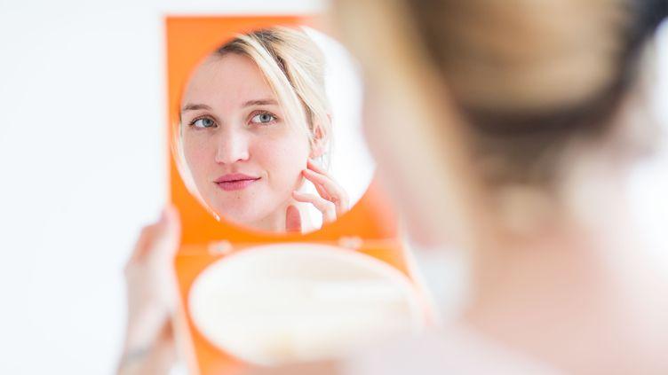 Une femme se regarde dans un miroir, à Paris, le 12 novembre 2015. (VOISIN / PHANIE)