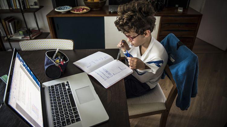 Un enfant fait ses devoirs pendant le confinement, le 23 avril 2020, à Toulouse (Haute-Garonne). (CELINE GAILLE / HANS LUCAS / AFP)