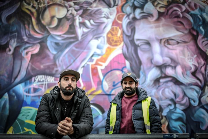 Antonio Sanchez Santos alias Pichi et Alvaro Hernandez Santaeulalia alias Avo,duo d'artistes de rue espagnol PichiAvo,posent devant leur œuvre peinte sur un mur du boulevard Saint-Michel à Paris. (STEPHANE DE SAKUTIN / AFP)