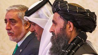 Le représentant du gouvernement afghan,Abdullah Abdullah (à gauche), et le négociateur en chef des talibans,Mullah Abdul Ghani Baradar (à droite), entourent le médiateur qatariMutlaq al-Qahtani lors de pourparlers de paix à Doha (Qatar), le 18 juillet 2021. (KARIM JAAFAR / AFP)