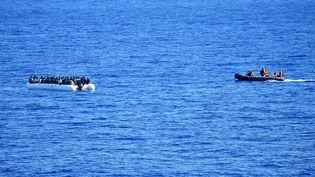 Desmigrantsoriginaires de plusieurs pays d'Afrique, attendent d'être secourus en mer, le 27 septembre 2015. (ALBERTO PIZZOLI / AFP)