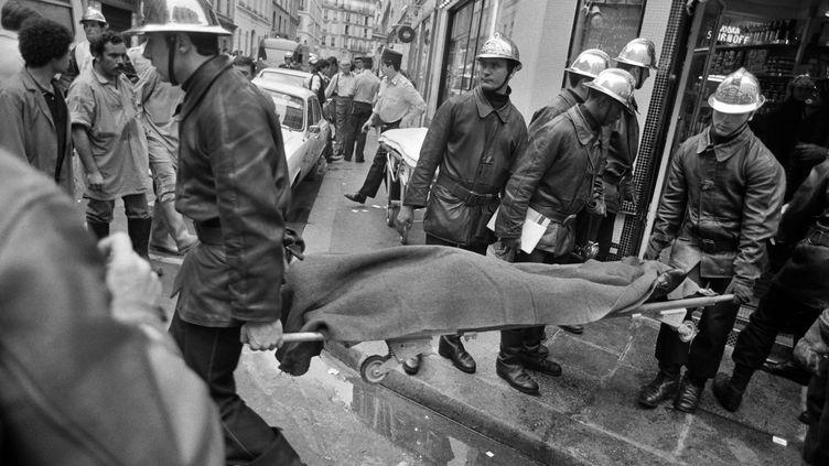 Une victime de l'attentat de la rue des Rosiers, évacuée par des pompiers, le 9 août 1982 à Paris. (MICHEL CLEMENT / AFP)