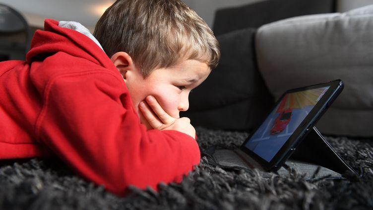 Un jeune garçon regarde son écran. (MAXPPP)
