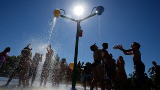 Des enfants se rafraîchissent sous des douches pendant la canicule. Photo d'illustration. (PATRICK HERTZOG / AFP)