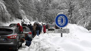 Des automobilistes installent des chaînes, le 30 décembre 2017, à Beaufort (Savoie). (JEAN-PIERRE CLATOT / AFP)
