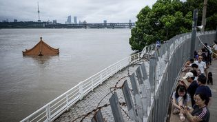 Des habitants regardent la montée du fleuve Yangtsé à Wuhan en Chine, le 12 juillet 2020. (AFP)