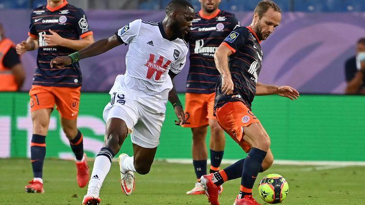 Le milieu de terrain de Bordeaux Junior Onana (C) se bat pour le ballon avec l'attaquant français de Montpellier Valère Germain (R) lors du match de football de L1 française entre Montpellier (MHSC) et Bordeaux (FCGB), au stade de La Mosson à Montpellier, le 22 septembre 2021. (PASCAL GUYOT / AFP)