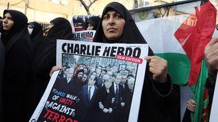 Téhéran (Iran), le 19 janvier 2015 : un photomontage représentant le chef de l'organisation Etat islamique (EI), Abou Bakr Al-Baghdadi, à côté de François Hollande, à Paris. (ATTA KENARE / AFP)