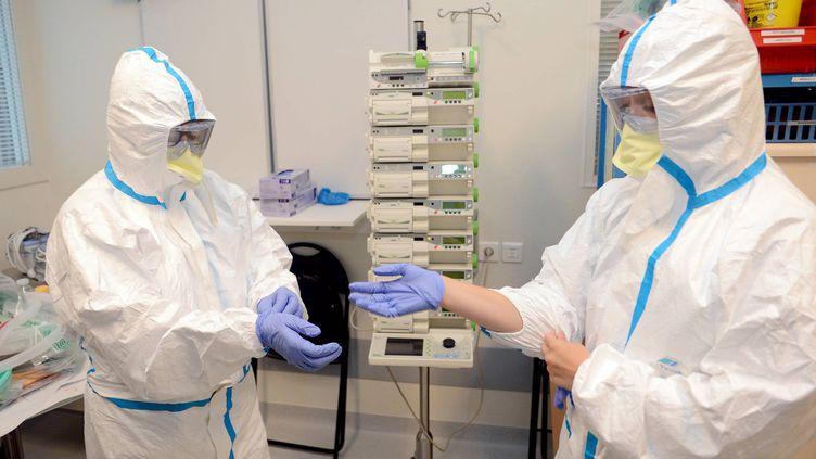 Deux infirmièress'équipent avec des combinaisons de protection dans une chambre à pression négative, au CHU de Rennes (Ille-et-Vilaine), le 12 août 2014. (  MAXPPP)