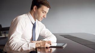 Un jeune cadre consulte une tablette. Photo d'illustration. (SIGRID OLSSON / MAXPPP)