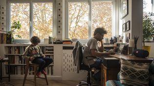 Un père télétravaille en présence de son enfant, le 14 novembre 2020 à Toulouse (Haute-Garonne). (CELINE GAILLE / HANS LUCAS / AFP)