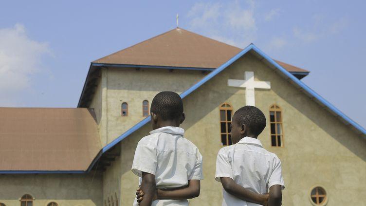 Deux enfants devant l'église catholique Emmanuel Butsili à Béni, le 27 juin 2021, après l'explosion d'une bombe de fabrication artisanale, juste une heure avant la tenue d'une cérémonie de confirmation. (SEBASTIEN KITSA MUSAYI / AFP)