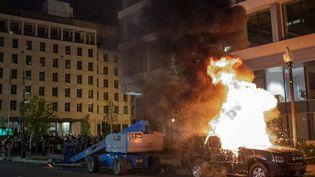 Une voiture enflammée à Washington (Etats-Unis), pendant des émeutes liées à la mort de George Floyd, le 30 mai 2020. (ERIC BARADAT / AFP)