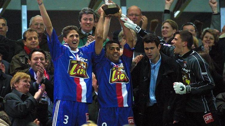 Anderson soulève la Coupe de la Ligue en 2001 aux côtés d'Edmilson et Coupet (MAXPPP)