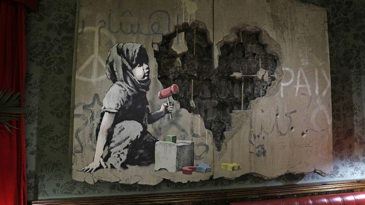 Une oeuvre de Banksy exposée au Walled-Off hotel de Bethlehem le 20 décembre 2019. (AHMAD GHARABLI / AFP)