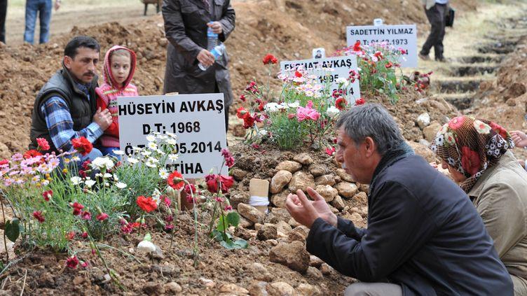 Des proches des victimes de l'accident minier de Soma, se recueillent sur les tombes des mineurs, samedi 17 mai, à Manisa (Turquie). (SONER KILINC / ANADOLU AGENCY)