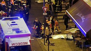 Un blessé est évacué près du bar Le Carillon et du restaurant Le Petit Cambodge, où des cadavres ont été couverts par des bâches, dans le 10e arrondissement de Paris, le 13 novembre 2015. (CHRISTIAN HARTMANN / REUTERS)