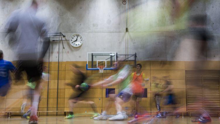 Des joueurs amateurs de handball dans un gymnase. Photo d'illustration. (JOHN MACDOUGALL / AFP)