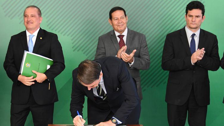 Le président brésilien Jair Bolsonaro signe un décret, le 15 janvier 2019, qui assouplit les règles de la détention d'armes à feu. (EVARISTO SA / AFP)