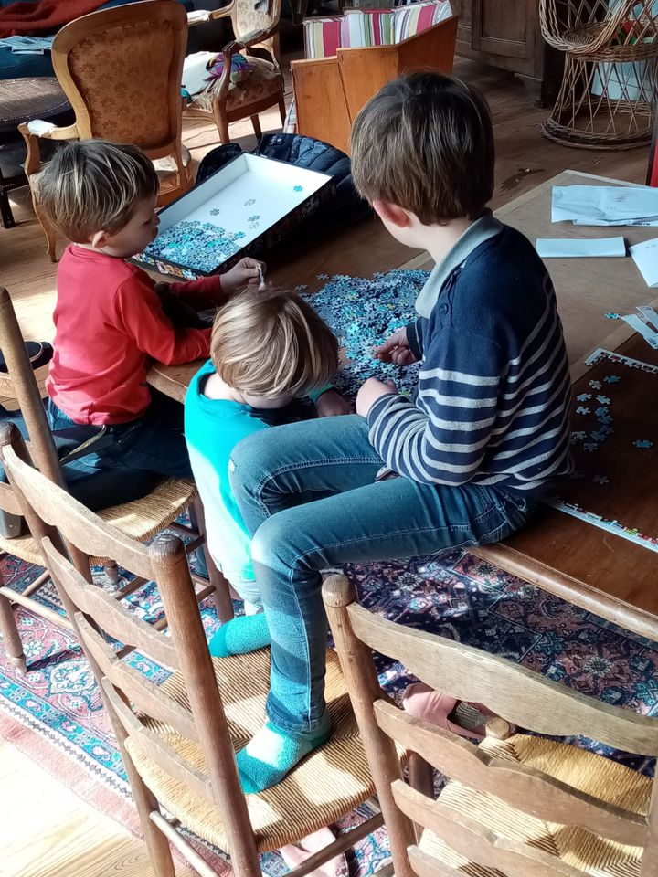 Trois des quatre enfants de Marie jouent au puzzle, le 20 mars 2020, dans leur maison de Gironde. (MARIE / FRANCEINFO)